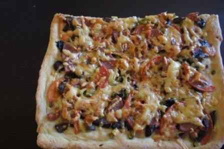 Готовая пицца с начинкой из грибов, колбасы, томатов, сыра