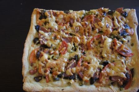 Готовая пиццы с начинкой из грибов, колбасы, томатов, сыра