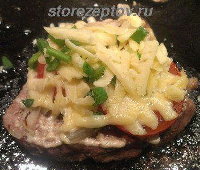 Куски свинины посыпанные сыром с зеленью