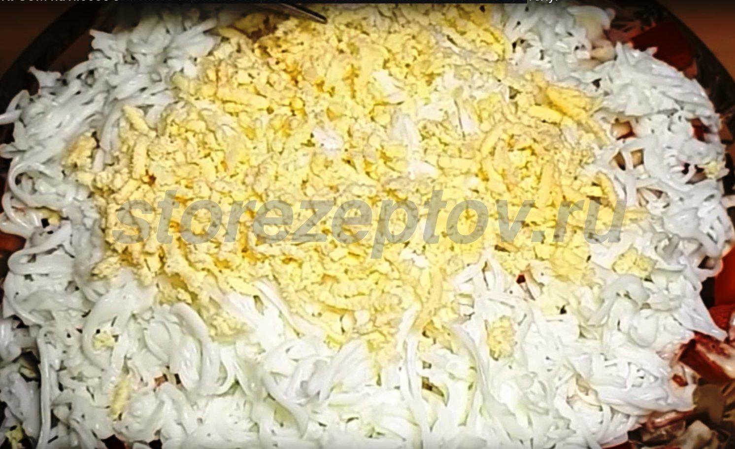 Посыпаем салат тертым белком и желтком