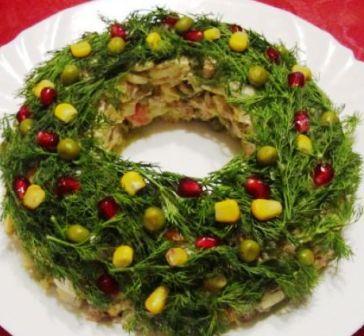 На фото украшенный укропом, зернами граната и кукурузой салат Рождественский венок